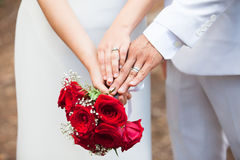 Just married couple compare their wedding rings while holding each others` hands and a bouquet. Large red roses. Couple just married showing wedding rings Royalty Free Stock Photography