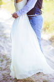 Just married couple embrace outdoor. The bride in a beautiful dress hugs groom on nature stock images