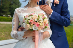 Just married couple embraced, and bride holding beautiful wedding flowers