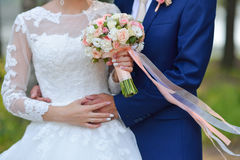 Just married couple embraced, and bride holding beautiful wedding flowers.  Stock Photo