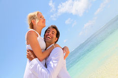 Just married couple having fun. Groom and bride laughing on a sandy beach Stock Images