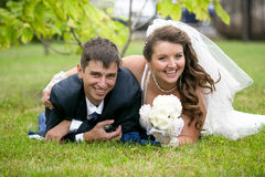 Just married couple having fun on grass at park Royalty Free Stock Image