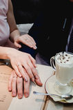 Just married couple hold hands and showing up wedding ring in cafe Stock Image