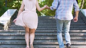 Just married couple holding hands and running upstairs, together towards success. Stock footage stock video footage