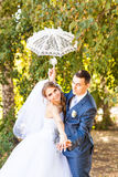 Just married couple holding white umbrella Royalty Free Stock Photography