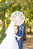 Just married couple holding white umbrella Stock Photos