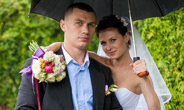 Just married couple hugging under umbrella Stock Image