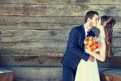 Just married couple kissing each other on wooden background Royalty Free Stock Photography