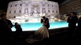 Just married couple kissing  in the front of the Trevi fountain. ROME, ITALY - MARCH 14, 2016: Just married couple kissing and posing in the front of the Trevi stock footage