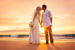 Just married couple kissing on tropical beach at sunset Stock Photos
