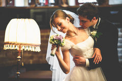 Bride smells a bouquet behind a vintage lamp while groom hugs her royalty free stock photos
