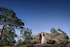 Just married couple looks at shining sun standing on the rocks Royalty Free Stock Image