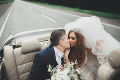 Just married couple in the luxury retro car on their wedding day Stock Photos