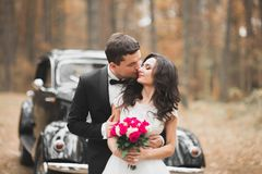 Just married couple in the luxury retro car on their wedding day.  Stock Photos