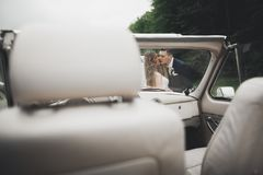 Just married couple in the luxury retro car on their wedding day.  Royalty Free Stock Image