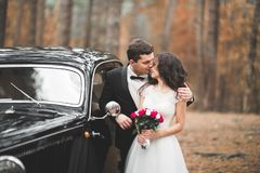 Just married couple in the luxury retro car on their wedding day.  Stock Photo