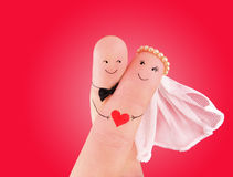 Just married couple - newlyweds painted at fingers against red. Just married couple, newlyweds painted at fingers against red background, good use for wedding royalty free stock photo