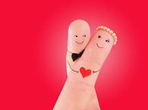 Just married couple - newlyweds painted at fingers against red. Loving couple painted at fingers against red royalty free stock photography