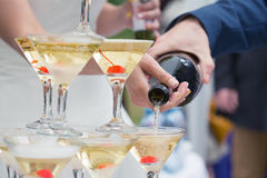 Just married couple pouring sparkling bubbly champagne into glasses Royalty Free Stock Images