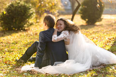 Just married couple relaxing on grass at autumn park Royalty Free Stock Photos