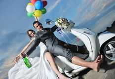 Just married couple ride white scooter Royalty Free Stock Image