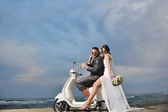 Just married couple ride white scooter Stock Image
