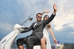 Just married couple ride white scooter Stock Photo