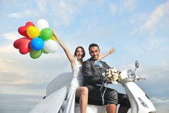 Just married couple ride white scooter Royalty Free Stock Images