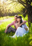 Just married couple siting under tree at park Royalty Free Stock Photo