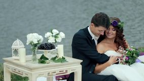 Just Married Couple Sitting Embraced Near a Pond stock video footage