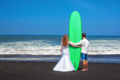 Just married couple stands with surfboard on sea beach Stock Photo