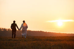 Just married couple walk towards a sunset holding their hands ti Stock Photo