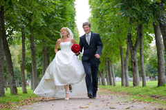 Just Married Couple Walking Fast Down The Path. Just married couple is walking fast down the path in the park. They are laughing Royalty Free Stock Images