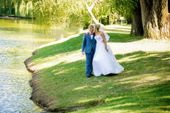 Just married couple walking at park near the lake a sunny day Stock Photo
