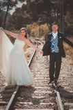 Just married couple walking on a railroad stock images