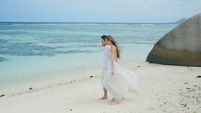 Just-married couple walking on tropical beach and kissing. A married couple in love, bride and groom, together walking on a beautiful tropical beach - Anse stock video footage