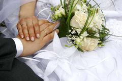 Just married - hands, rings, bouquet. Young just married couple shows their hands with wedding rings Royalty Free Stock Images