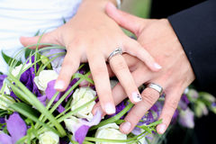 Hands of a newly wed couple together Stock Photography