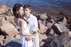 Just married happy couple on a rocky beach Stock Images