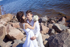 Just married happy couple on a rocky beach Stock Image