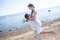 Just married happy couple running on a sandy beach Royalty Free Stock Image