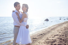 Just married happy couple running on a sandy beach Stock Photography