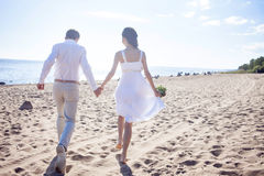 Just married happy couple running on a sandy beach Stock Photo