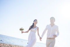 Just married happy couple running on a sandy beach Royalty Free Stock Photography