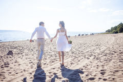 Just married happy couple running on a sandy beach. Just married couple running on a sandy beach Royalty Free Stock Photo