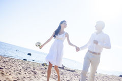 Just married happy couple running on a sandy beach Royalty Free Stock Photo