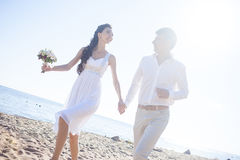 Just married happy couple running on a sandy beach. Just married couple running on a sandy beach Stock Image