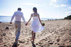 Just married happy couple running on a sandy beach, view from the back. Just married couple running on a sandy beach Royalty Free Stock Images