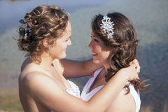 Just married happy lesbian couple in white dress near small lake. Just married happy lesbian couple in white dress look each other happily in the eyes near small Stock Images