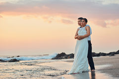 Just married happy young couple. Stand on ocean beach sunset colorful background Stock Photography